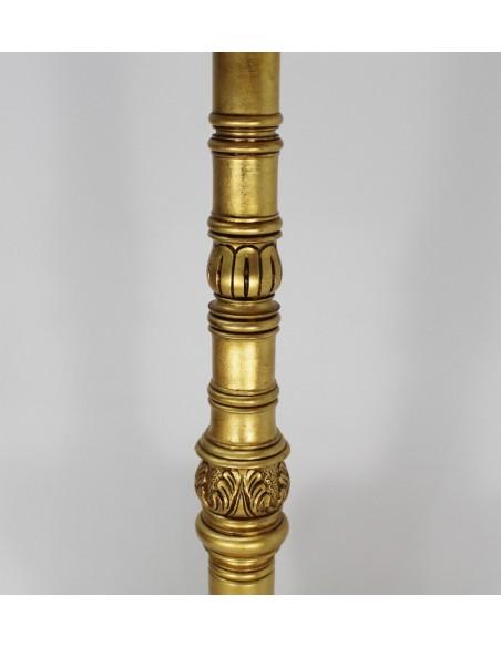 Atril de madera tallada acabado en oro. Pie con motivos de volutas y escocias de cuatro patas con volutas.  Altura: 125 cm.