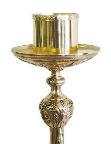 Portacirio de bronce con acabado en dorado y base ancha con detalles florales.