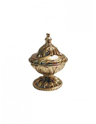 Naveta de bronce en acabado dorado.  Esta compuesta de diversos labrados con detalles florales. Medidas: 13 cm de alto x 8 cm