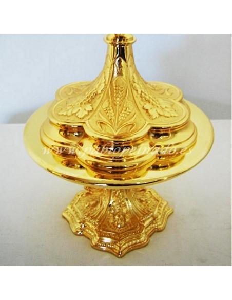 Custodia de metal con acabado dorado y decoración de espigas y vides. Base trebolada con los mismos motivos decorativos. Dimens