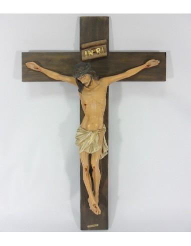 Crucifijo de pared con cruz lisa y cristo en color. El crucifijo está en un color oscuro y tiene tablones anchos con una altur
